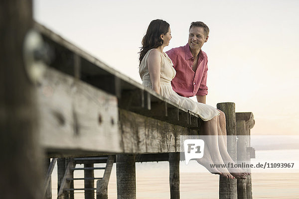 Mature couple looking at each other and smiling on pier  Bavaria  Germany