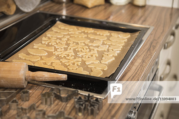 Baking tray with different shaped cookies on kitchen counter