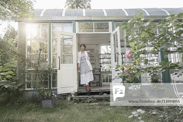 Senior woman standing in a greenhouse  Bavaria  Germany Senior woman standing in a greenhouse, Bavaria, Germany
