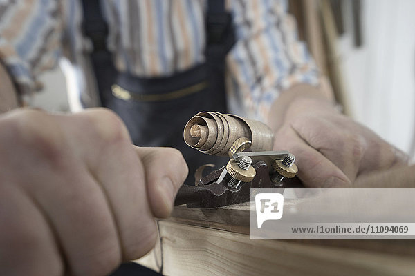 Male bow maker shaving wood and giving it a shape of bow in workshop  Bavaria  Germany