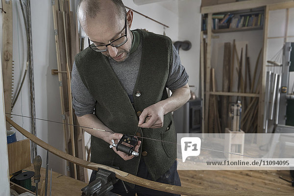 Male bow maker adjusting bow string in workshop  Bavaria  Germany Male bow maker adjusting bow string in workshop, Bavaria, Germany
