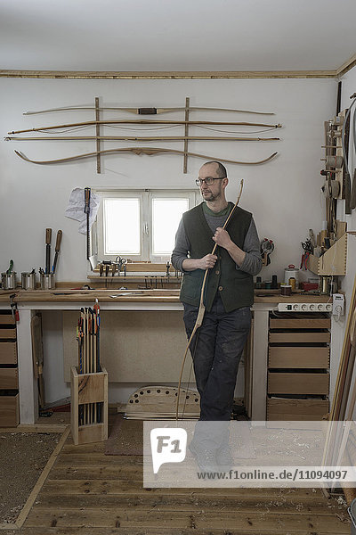 Male bow maker holding bow and thinking in workshop  Bavaria  Germany