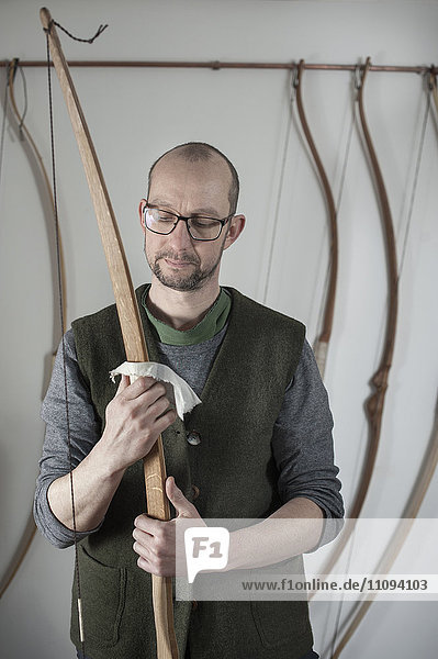 Male bow maker polishing bow in workshop  Bavaria  Germany