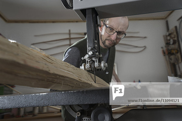 Male bow maker sawing wood with a bandsaw  Bavaria  Germany Male bow maker sawing wood with a bandsaw, Bavaria, Germany