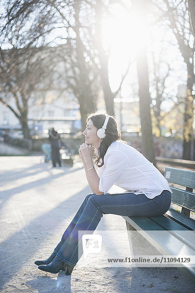 Mature woman listening to music and sitting in the park bench  Bavaria  Germany