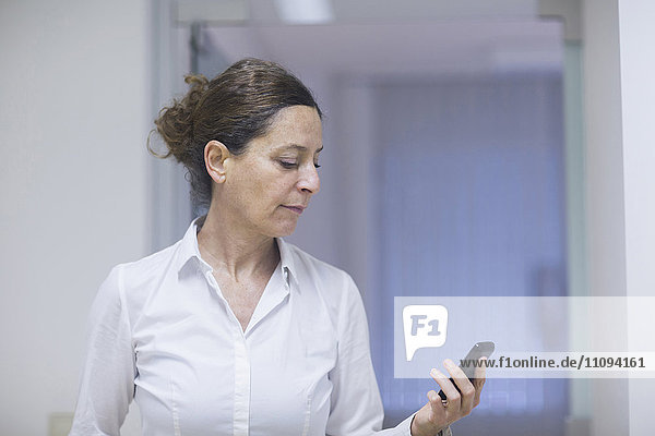 Female physiotherapist reading message on a mobile phone