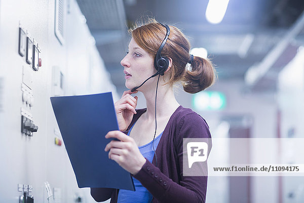 Young female engineer wearing headset and controlling a switch gear in control room