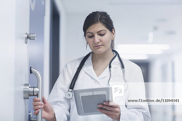 Young female doctor using a digital tablet in hospital corridor