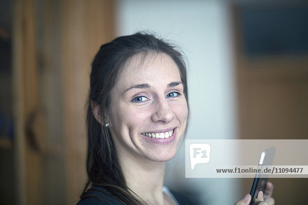 Portrait of a young woman holding digital tablet and smiling
