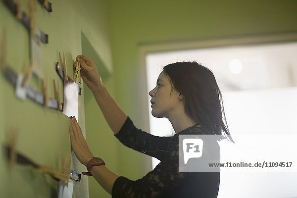 Side profile of a businesswoman hanging paper with clips in an office