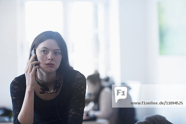 Businesswoman talking on mobile phone in an office