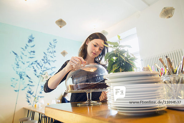 Young woman holding lid on cakestand in coffee shop