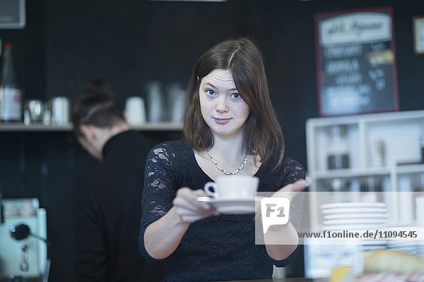 Young waitress serving coffee in coffee shop