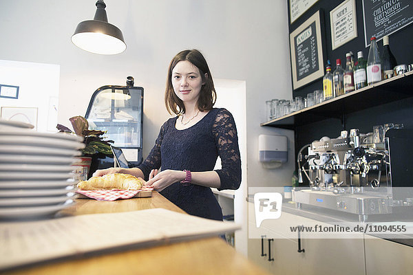 Young woman working in coffee shop serving croissant