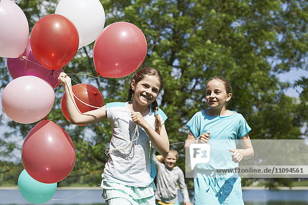 Girls running in park with balloons  Lake Karlsfeld  Munich  Bavaria  Germany