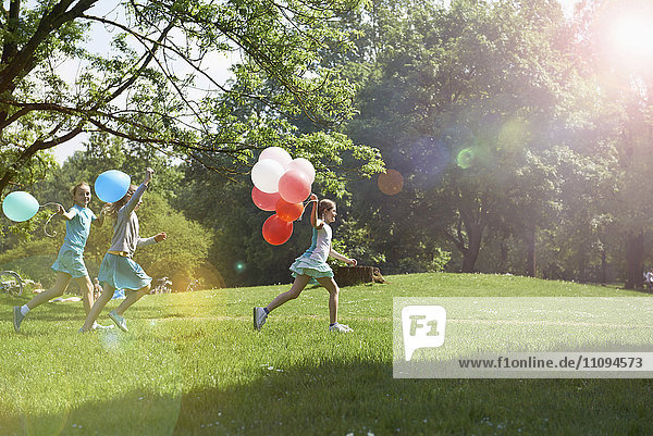 Girls running in park with balloons  Munich  Bavaria  Germany