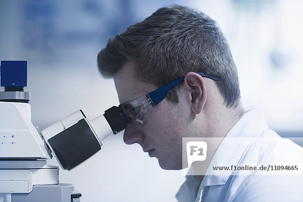 Young male scientist looking through microscope in an optical laboratory