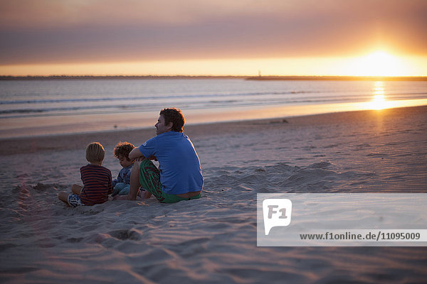 Father with two kids sitting on beach during sunset  Viana do Castelo  Norte Region  Portugal
