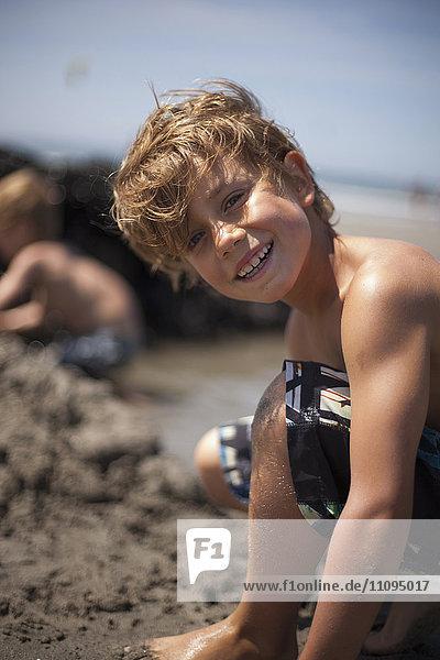 Portrait of a boy building a sandcastle and smiling on the beach  Viana do Castelo  Norte Region  Portugal