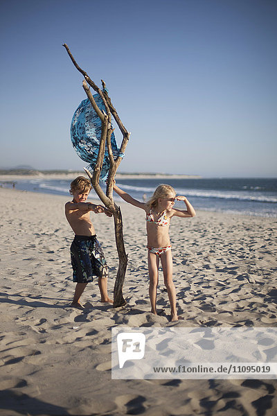Two children playing with wood on the beach  Viana do Castelo  Norte Region  Portugal