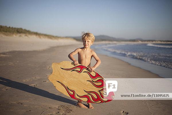 Little boy holding sandboard on the beach  Viana do Castelo  Norte Region  Portugal
