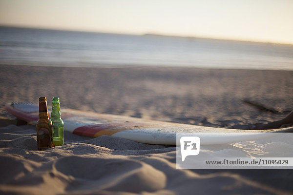 Two beer bottles with surfboard on the beach during sunset  Viana do Castelo  Norte Region  Portugal