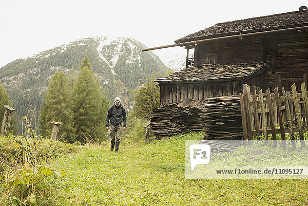 Mature hiker passing by cottage at rainy day  Austrian alps  Carinthia  Austria