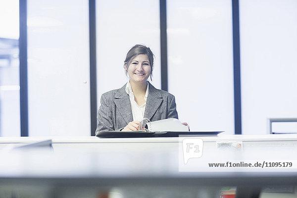 Businesswoman reading document and smiling in office  Freiburg Im Breisgau  Baden-Württemberg  Germany