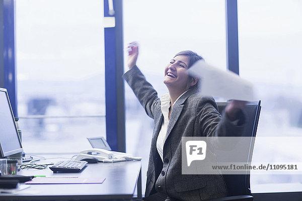 Excited businesswoman celebrating her success in an office  Freiburg Im Breisgau  Baden-Württemberg  Germany