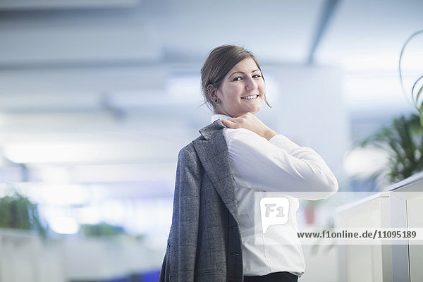 Businesswoman carrying suit on her shoulder and smiling in office  Freiburg Im Breisgau  Baden-Württemberg  Germany