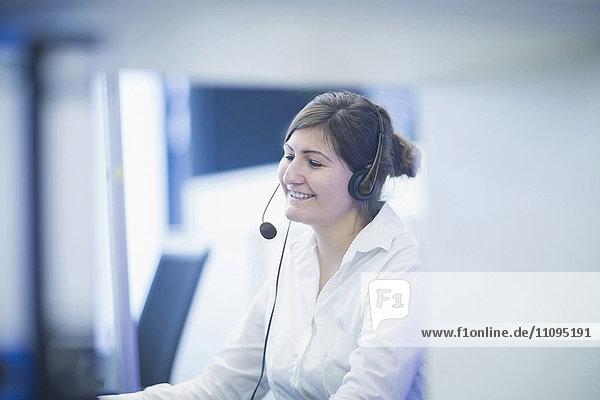 Happy businesswoman wearing headset and working in office  Freiburg Im Breisgau  Baden-Württemberg  Germany