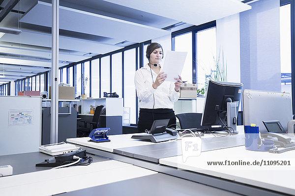 Businesswoman standing and reading document in office  Freiburg Im Breisgau  Baden-Württemberg  Germany