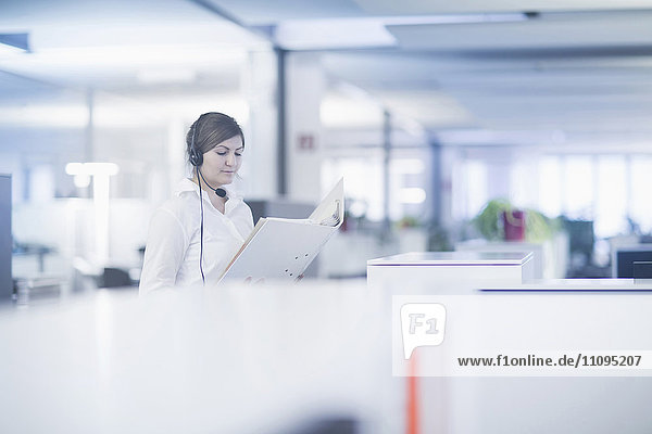 Businesswoman wearing headset and reading document in cubicle  Freiburg Im Breisgau  Baden-Württemberg  Germany