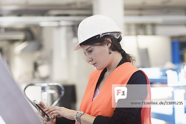 Female engineer using a smart phone in an industrial plant  Freiburg Im Breisgau  Baden-Württemberg  Germany