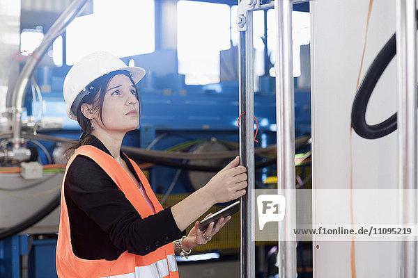Female engineer using a digital tablet and examining the machine in an industrial plant  Freiburg Im Breisgau  Baden-Württemberg  Germany