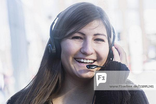 Portrait of a young woman smiling talking on headset  Freiburg im Breisgau  Baden-Württemberg  Germany