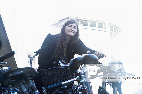 Young woman standing with bicycle in parking lot  Freiburg im Breisgau  Baden-Württemberg  Germany