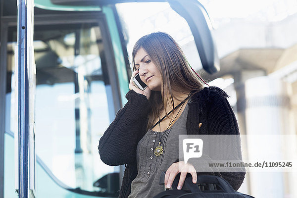 Young woman talking on mobile phone and standing in front of bus  Freiburg im Breisgau  Baden-Württemberg  Germany