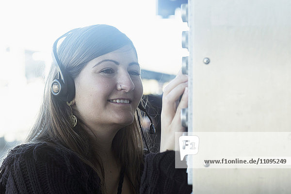 Young woman wearing headset and controlling switch  Freiburg im Breisgau  Baden-Württemberg  Germany