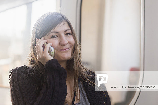 Portrait of a young woman talking on mobile phone in front of a train  Freiburg im Breisgau  Baden-Württemberg  Germany