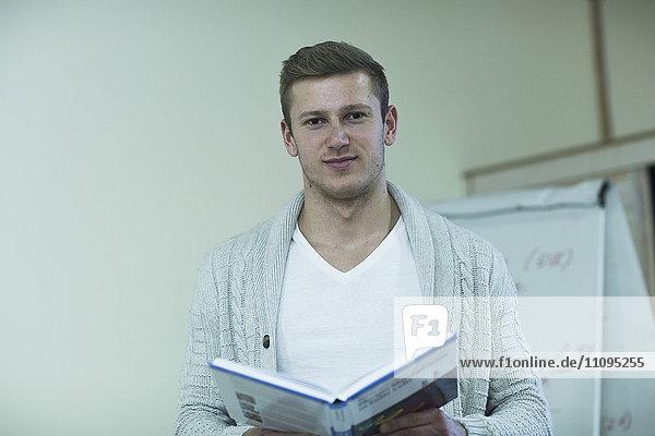 Young male teacher teaching in classroom  Freiburg Im Breisgau  Baden-Württemberg  Germany