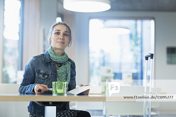 Mature female traveller with luggage sitting at table and looking at hotel menu  Freiburg Im Breisgau  Baden-Württemberg  Germany