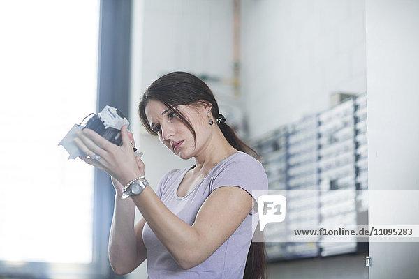 Female technician examining electrical component in an industrial plant  Freiburg Im Breisgau  Baden-Württemberg  Germany