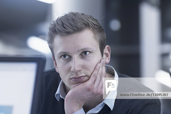 Young businessman thinking and working till late night in office  Freiburg im Breisgau  Baden-Württemberg  Germany