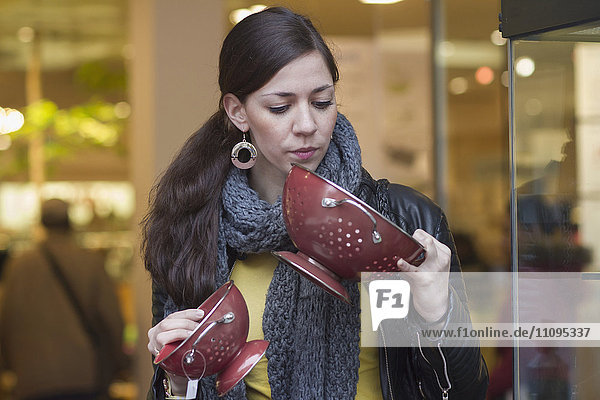 Young woman choosing colanders in the shop  Freiburg im Breisgau  Baden-Württemberg  Germany