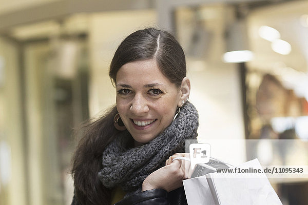 Portrait of a young woman with shopping bag in the shop and smiling,  Freiburg im Breisgau,  Baden-Württemberg,  Germany