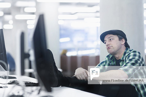 Mid adult man sitting in the office and thinking  Freiburg im Breisgau  Baden-Württemberg  Germany