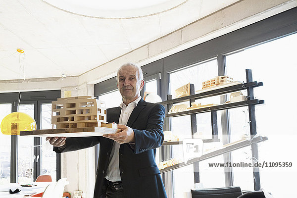 Portrait of a senior architect showing architectural model in the office  Freiburg im Breisgau  Baden-Württemberg  Germany
