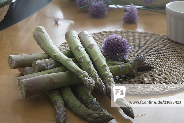Pile of asparagus with flower on table
