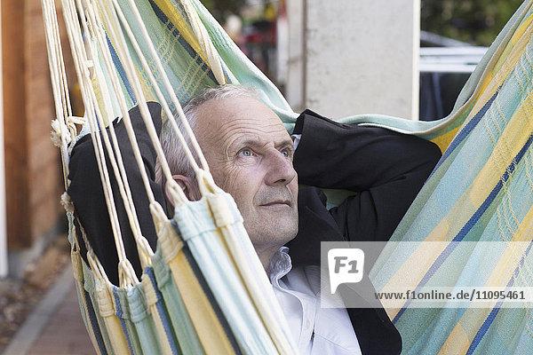 Close-up of a senior businessman lying on hammock and thinking  Freiburg im Breisgau  Baden-Württemberg  Germany